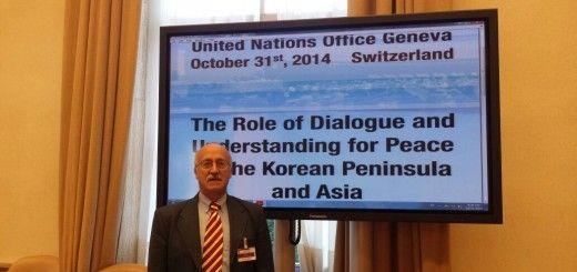 """Santiago Castillo junto al cartel anunciador del foro sobre """"La Paz, Diálogo y Unificación en la península coreana"""", en la sede de la ONU, en Ginebra"""